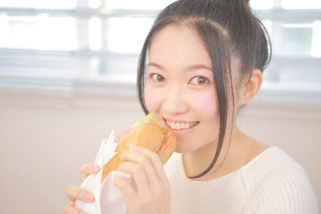 カフェでパンを食べる女性