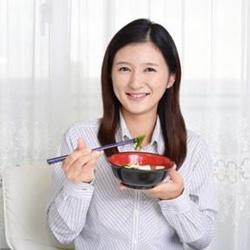 味噌汁を飲む女性